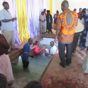 The new believers are baptized in the borrowed baptistery of a sister church.
